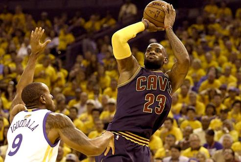 Cleveland Cavaliers forward LeBron James (23) shoots against Golden State Warriors forward Andre Iguodala (9) during the first half of Game 1 of basketball's NBA Finals in Oakland, Calif., Thursday, June 4, 2015. (AP Photo/Ben Margot)